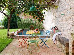 Muebles de colores sobre verde y piedra