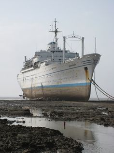 The recently-beached Anastasis, the former Lloyd Triestino liner Victoria of 1953, reveals her classic Italian lines at low tide. (photo by Peter Knego)
