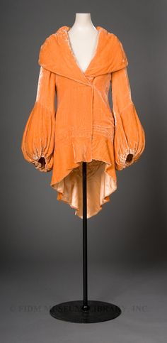 Orange silk panné velvet evening coat, c. 1930-32. Evening gowns of the 1930s were usually floor-length and clung to the body. Made of silk or velvet, they were cut on the bias and often exposed a swath of bare back or shoulder. Of course, this exposure meant that a fashionable evening coat was necessary in the colder months. Though black was encouraged as a practical, wear-with-everything choice, another option would have been an evening coat in an intense shade of purple, raspberry red…