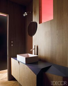 An angular oak cabinet encloses the bath of a contemporary Paris apartment designed by Andrea Marcante and Adelaide Testa of the Italian firm UdA. A red-glass window lets in light from the adjacent bedroom; the sink is by Flaminia, and the fittings are by Palomba.   - ELLEDecor.com