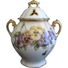 R Delinieres & Co (D & Co) A late 19th century~French porcelain covered urn~It is lavishly decorated with pansy floral regalia~artist signed~Dated 1893