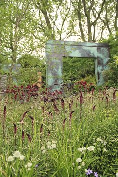 Love the weathered bronze archway juxtaposed with the prairie style perennial planting