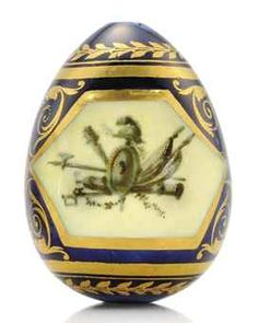 A PORCELAIN EASTER EGG BY THE IMPERIAL PORCELAIN FACTORY, ST PETERSBURG, CIRCA 1800. Ovoid, each side centring a hexagonal cartouche painted en grisaille with martial trophies over a pale yellow ground, within gilt borders, the sides decorated with ciselé gilt scrolling acanthus centring a rosette on a royal blue ground, within gilt borders and berried laurel bands, apparently unmarked.