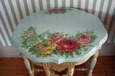 A CHALK PAINTED ORNATE VINTAGE ACCENT TABLE IN CREAM & BLUE. TOP IS PAINTED BLUE W/ROSES PAINTED IN PURPLE,GREEN.PINK,YELLOW & RUSTIC ORANG. ACCENT UR ROMANTIC COUNTRY,ROMANTIC COTTAGE,FRENCH COUNTRY,BLUE,YELLOW,GREEN,PURPLE,PINK & OR RUSTIC ORANGE COLOR SCHEMED DECORS.CHERIE