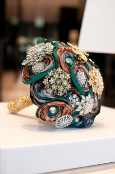 Neat idea if i dont collect enough brooches! Turquoise and orange brooch boquet