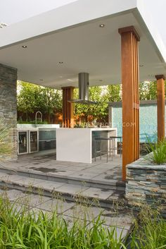 Outdoor Kitchen & Covered Patio home landscaping with dining table, waterfall water feature, ornamental grasses plants, hood, modern design, stairs steps, deck, refrigerator, sink, oven, classy and sophisticated room for cooking and eating outside