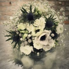 Winter white wedding bouquet. Anemones, Ranunculus, Gypsophila, Eryngium, Spray Roses & Brunia berries