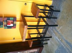 """Pub table and stools with iron base and natural edge 3"""" cypress as table top and seats."""
