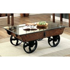 Refined rustic designs are complimented with industrial accents to create a tribute to the hard-working laborer. This glass top coffee table features eye-catching metal detailing while the weathered wood exterior enhances the wheelbarrow structure.