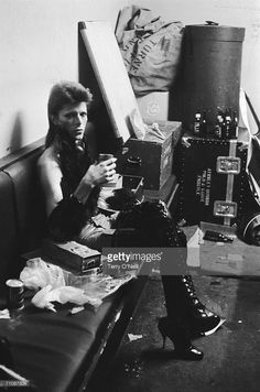 English singer David Bowie, backstage, circa 1973. He is wearing high heeled black patent leather boots.
