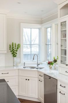 Beautiful naturally lit kitchen features a corner under-mount sink against a set of tall white framed windows.