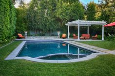 Pretty design for a Swimming Pool, and pops of color on the exterior design with orange cushion accents offered via patio furniture.