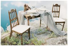 Rustic wedding inspiration. Aged wood table with vintage chairs, a centerpiece of blush roses and natural wood and place settings of white china on hand dyed silk with beautiful glassware and place cards of natural paper and white calligraphy. Styling and florals by Janna Brown Design Co., silk by Silk & Willow, calligraphy by Linen & Leaf. Image by Sleepy Fox Photography.