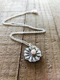 Sterling silver flower necklace. Comes with a pearl on a delicate sterling chain. Simple and pretty!