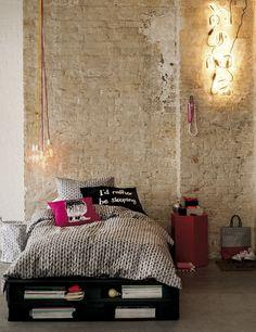 Fiebre DIY Unos palés funcionan como cama en este espacio de H&M Home: funda nórdica, y cojines