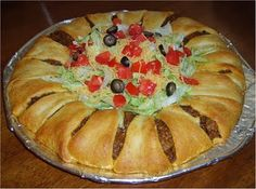 Baked Taco Ring(30 min. to bake)  1 lb. ground beef  1 package (1.25 oz) taco seasoning mix  1 c. (4 oz) shredded cheddar cheese  2 tbs water  2 8-oz packages refrigerated crescent rolls  1 medium green bell pepper  1 c. salsa (optional)  3 c. lettuce, shredded (we used more — ¾ a head)  1 medium tomato, diced  ¼ c. onion, chopped  ½ c. pitted ripe olives  sour cream
