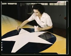 """WWII era photo:  """"Women from all fields have joined the production army, Corpus Christi, Texas. Miss Grace Weaver, a civil service worker at the Naval Air Base, and a school teacher before the war, is doing her part for victory along with her brother who is a flying instructor in the Army. Miss Weaver paints the American insignia on repaired Navy plane wings."""" Visual reference for the Duster graphic novel. http://Duster.me"""