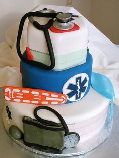 EMT Parametics three tier custom wedding cake with edible blood pressure cuff, glove, hearts, back board, Stethoscopes and oxygen tank. The Bride and Groom's heart beats are on edible EKG paper