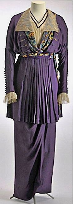 Ensemble ca. 1912-13. Tunic dress in silk satin. Representative of the fashion for Orientalism, dress has bright colors, including purple, orange, black, & jade green, in sharply defined print used to finish shawl color, buttons, buttonholes, & waistband. Lapels in embroidered silk voile attached to collar. Blouse is ecru silk voile, pleated. Silhouette is broad at top, with batwing sleeves, and narrows to hobble skirt at ankles. Mode Museum, Hasselt
