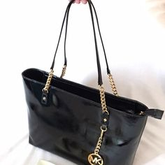 NWT Michael Kors Jet Set Chain Black Leather Tote Brand New With Tags Beautiful Authentic Michael Kors Jet Set EW Black Patent Leather Tote With Double Gold Chain And Leather Straps. Top zip closure and MK Logo Keychain Hangtag. Comes with dust bag and MK care card. Michael Kors Bags Totes