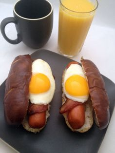 Breakfast Hot Dogs - Pretzel buns topped with country gravy and 1/4 pound hot dogs wrapped in Applewood smoked bacon, plus a sunny side up egg on each one.