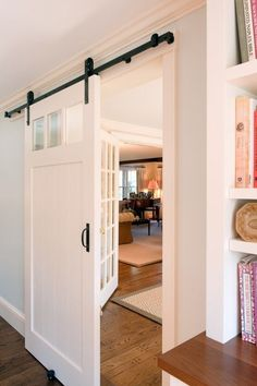 In addition to the rustic look, barn doors used in modern interiors can still be refined. With this example, the function of the door is what it's all about, blending into a refined and stately look and feel, and creating a seamless transition between zones in a home. The transition strategy here is less about contrast than the one above. Yet, the barn style sliding door still manages to be a feature from one room to another.