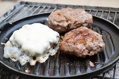 Cocinando hamburguesas en la parrilla Le Creuset sobre carbón