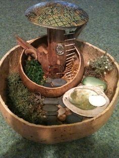 "fairy gourd house created with a piece of cedar,gourd ""roof"" and nestled inside a gourd-nestled inside a bigger gourd. For garden accents or indoors"