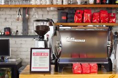 Cute silver La Marzocco espresso machine and red packaging. Industrial.