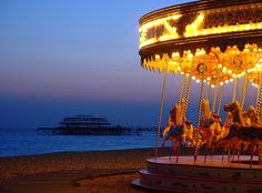 Carousel | The flying horse carousel on Brighton beach. In the background is the frame of the West Pier - pictured subsequent to the fire, but before storm damage caused it to collapse. 2003