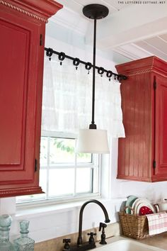 Red painted cabinets....black accents and light. The Lettered Cottage