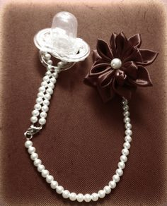 DIY pacifier clip. Got the flower from Joanns. It already had the clip on the back of it. Strung some fishing line with pearls and attached it to the flower and some fasteners.