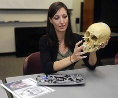 Baltimore County Detective Evelyn Grant is also a forensic artist. Here, she holds a model of a human skull. Her drawing tools and a recent drawing are on left. (Barbara Haddock Taylor, Baltimore Sun)