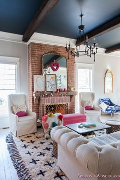 Inside Our Colorful, Whimsical & Elegant Valentine's Day Living Room... Take a peek inside our 1905 historic home all decked out with Valentine's decor!    gossamer-veil-sherwin-williams-alabaster-inkwell-black-ceiling-dark-wood-beams-brick-fireplace-reclaimed-mantle-cross-shag-rug-gold-fireplace-screen-skirted-cream-parsons-chairs-chesterfield-tufted-sofa-anthropologie-white-marble-coffee-table-wood-side-pedestal-pink-velvet-bench-gold-mirror