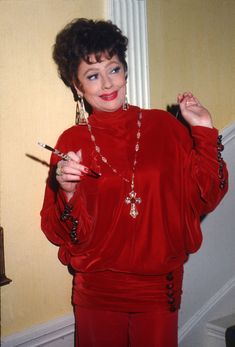 1974: Attending a party thrown in her honor donning a chic scarlet gown and chunky jewelry. - TownandCountrymag.com