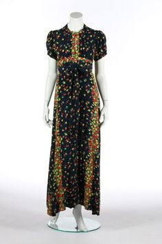 An Ossie Clark/Celia Birtwell floral printed navy crepe evening dress, 1971. printed Radley label, the bodice with pleats and centre-front opening, tie to neck, wrap-around skirt with ties and low back, bust approx 92cm, 36in . - See more at: http://kerrytaylorauctions.com/one-item/?id=184&auctionid=401#sthash.0sXBvCP3.dpuf