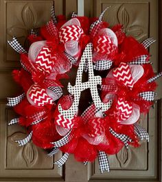 """This is a 24"""" Alabama Crimson Tide deco mesh wreath. It is red and white and silver and has red and white chevron ribbon and houndstooth ribbon accents on it. It also has a houndstooth wooden A decora"""