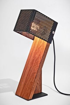 Combining solid wood and acrylic, Jonathan Dorthe's Oblic Table Lamp does what its name implies, stands obliquely, a slanted wooden pedestal with a plastic cage for the light source.