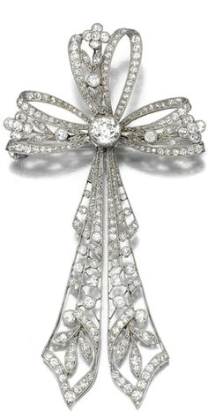 DIAMOND BROOCH, CIRCA 1910 Designed as an open work tied ribbon bow, millegrain-set with circular-cut diamonds, detachable brooch pin and pendant bail to the reverse