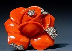 Cartier. A striking coral and diamond flower brooch. Paris, circa 1960. ~ depicting a carved coral rose, the petals with brilliant cut diamond details and brilliant cut diamond dew drop, mounted in platinum and 18 karat gold. Signed Cartier