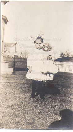 A sweet little girl with a huge hair bow poses in her front yard with her treasured doll! You can see the photographers shadow in the photo