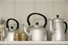 Love the display of different metal coffee pots.