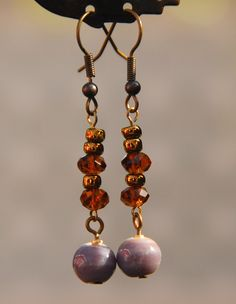 Simple, yet chic, vintage look earrings featuring ceramic and faceted glass beads        Matching necklace available at: http://www.luulla.com/product/24185/brown-and-purple-shell-ceramic-and-glass-necklace        Length: 2.25 inches from top of earwire