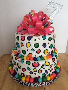 """Rainbow Leopard Cake - This is my daughter's 7th birthday cake. 8"""" & 10"""" rounds. Strawberry cake with banana-chocolate filling. Covered with fondant and hand-painted. Fondant-loop bow with fondant curlicues and fondant ball border."""