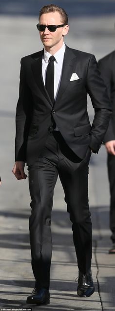Perfect gent: The rangy English actor looked sharp in a shiny black suit with white shirt and black tie and  he wore a folded white handkerchief in his breast pocket