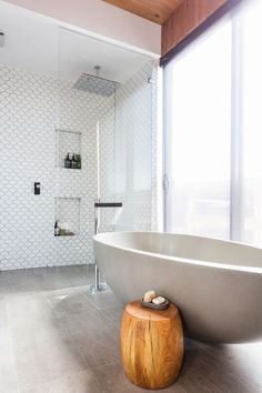 i like the combo of the shower tiles, floor tiles, stand alone bath and big chunky wooden stool/table