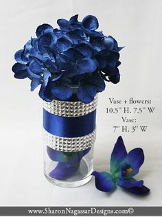 """This listing includes:  1 - Silk flower wedding centerpiece. Designed with silk hydrangea in navy blue color.  Flowers is set in floral foam in a glass cylinder vase. Vase is decorated with navy blue band and 2 rhinestone crystal bands.  Each rhinestone crystal band is approx 1"""" wide. Vase size: 7.5"""" tall, 3"""" wide. Vase + flowers: 10.5"""" tall, 7.5"""" wide Blue orchid outside vase is not included. Can be purchased separately - $4.90  Other centerpiece/hydrangea color..."""