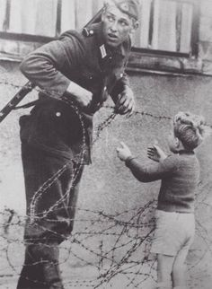 """1961 - Construction on the Berlin Wall began. Photo caption: """"An East German soldier helps a young boy cross the barbed wire which was a marker for where the Berlin wall would soon be built. The guard was caught and punished. Papua Nova Guiné, German Soldier, German Army, Faith In Humanity Restored, Photo Caption, Berlin Wall, Anne Frank, Interesting History, Interesting Photos"""