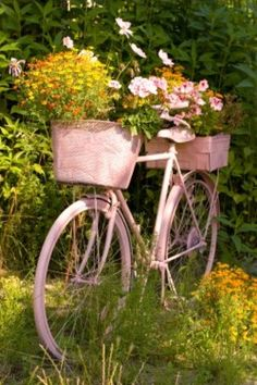 Pink bicycle repurposed to a flower pot.