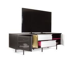 """Holds most 65"""" TVs. Two drawers. Two adjustable shelves. Two ventilated doors. Black textured and gloss white metal. Brass-plated and hot pink accents..."""